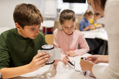 Happy children building robots at robotics school. Education, children, technology, science and people concept - group of happy kids building robots at robotics Royalty Free Stock Image