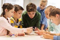 Happy children building robots at robotics school. Education, children, technology, science and people concept - group of happy kids building robots at robotics Royalty Free Stock Photos