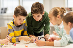Happy children building robots at robotics school. Education, children, technology, science and people concept - group of happy kids building robots at robotics Stock Photo