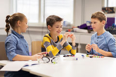 Happy children building robots at robotics school. Education, children, technology, science and people concept - group of happy kids building robots at robotics Royalty Free Stock Photo