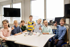 Happy children building robots at robotics school. Education, children, technology, science and people concept - group of happy kids building robots at robotics Royalty Free Stock Images