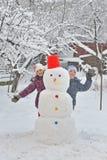 Happy children building snowman Stock Photos