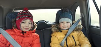 Happy children in the car in the back seat winter trip.  stock images