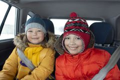 Happy children in the car in the back seat winter trip.  stock photo