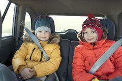 Happy children in the car in the back seat winter trip Royalty Free Stock Image
