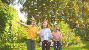 Happy children on carnival party under flying confetti in summer park. stock video