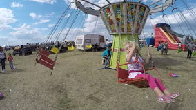 Happy children in a carousel chains country fair in Romania video Royalty Free Stock Photography