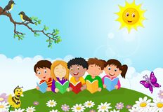 Happy children cartoon sitting on the grass while reading books Royalty Free Stock Photography