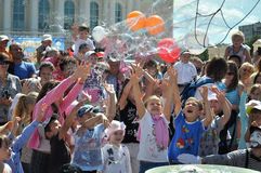 Happy children catch soap bubbles on the square at Dramatic thea. Ter in Tyumen, Russia. July, 2015 stock photos