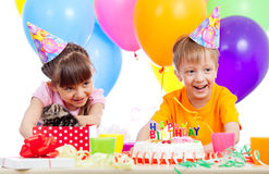 Happy children celebrating birthday party. With kitten in opening gift box stock images