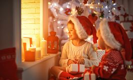 Happy children with christmas presents near Christmas tree and f Royalty Free Stock Image