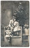 Happy children Christmas tree gifts vintage toys. Happy children with Christmas tree, gifts and vintage toys. Antique sepia picture with original film grain and stock photography