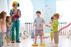 Happy children and clown on birthday party. Indoors stock photography