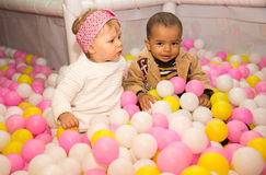 Happy children in colored ball on birthday on playground. Royalty Free Stock Photos