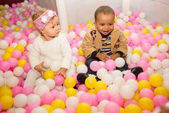 Happy children in colored ball on birthday on playground. Stock Photo