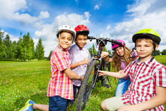 Happy children in colorful helmets repair bicycle royalty free stock image
