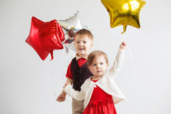 Happy children with colorful shiny foil balloons against a white Stock Photos