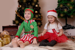 Happy children in costumes opening Christmas gifts Stock Photo