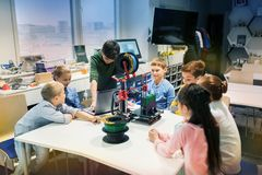 Happy children with 3d printer at robotics school. Education, children, technology, science and people concept - group of happy kids with 3d printer and laptop stock images