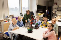 Happy children with 3d printer at robotics school. Education, children, technology, science and people concept - group of happy kids with 3d printer and laptop Royalty Free Stock Images
