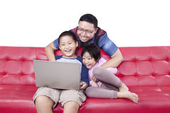 Happy children and dad use laptop on sofa Stock Photo