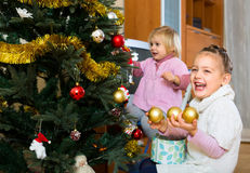 Happy children decorating a fir Royalty Free Stock Photography