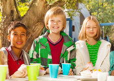 Happy children diversity sitting at table outside. Happy children diversity sitting at wooden table outside with cups and cupcakes during sunny autumn day Royalty Free Stock Images