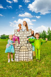 Happy children diversity in theatric costumes play. Happy diversity of children in theatric costumes play around drawn tower and having fun Royalty Free Stock Image