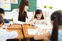 Children drawing in the classroom and teacher. Happy children drawing in the classroom and teacher near by Royalty Free Stock Images