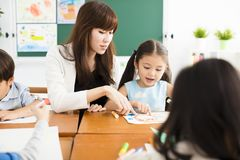 Children drawing in the classroom and teacher. Happy children drawing in the classroom and teacher near by Stock Image