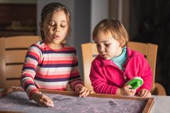 Happy Children Drawing Pictures on Black Chalk Board royalty free stock image