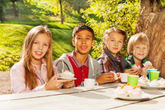 Happy children drinking tea with cupcakes Stock Photos