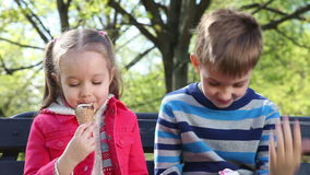 Happy children eating ice cream. Two happy children eating ice cream on bench in the park at the day time stock video