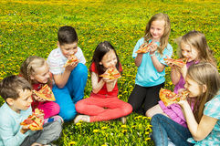 Happy children eating pizza outdoors Stock Photo
