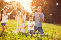 Happy children enjoying in chasing soap bubbles. Happy children with parents enjoying in chasing soap bubbles royalty free stock photos