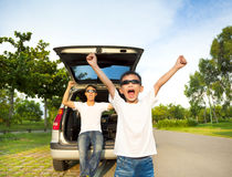 Happy children and father raise arms with their car Stock Photo