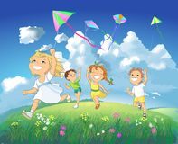 Happy children flying kites. Stock Photos