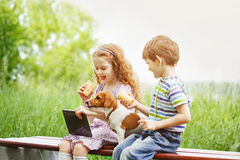 Happy children with a friend puppy dog playing in the tablet PC stock image