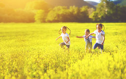 Happy children friends sisters run and play outdoors. On the meadow Stock Photography