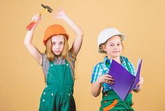 Happy children. Future career. small girls repairing together in workshop. Labor day 1 may. Little kids in helmet with royalty free stock image