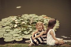 Happy children. Future and flourishing. Children happy smile on green lake landscape. Summer vacation concept. Girls sit on grass at pond with water lily stock photo