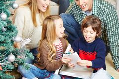 Children getting presents at christmas eve. Happy children getting presents from their parents at christmas eve royalty free stock image