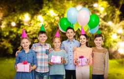 Happy children with gifts at birthday party. Childhood, birthday, friendship and people concept - happy smiling children in party hats with gifts and balloons stock photo