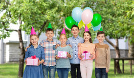 Happy children with gifts on birthday party. Childhood, holidays, friendship and people concept - happy smiling children in party hats with gifts and balloons on royalty free stock images