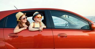 Happy children girl and boy goes to summer travel trip in car. Happy children girl and boy goes to summer travel trip in the car stock photos