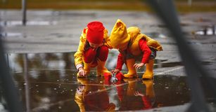 Happy children girl and boy with paper boat in puddle in autumn Stock Photo