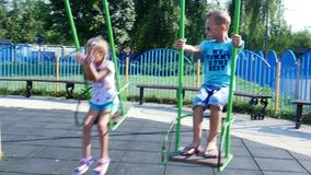 Happy children, a girl and a boy of seven, ride on a swing, on a hot summer day. Slow motion. Cheerful happy childhood stock footage
