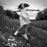 Happy children girl jumping on spring poppy flowers. Meadow with motion blur Royalty Free Stock Photography