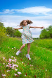 Happy children girl jumping on spring poppy flowers. Meadow with motion blur Stock Image