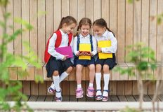 Happy children girlfriends schoolgirls student elementary schoo. Happy children girls girlfriends schoolgirls student elementary school with a smartphone royalty free stock photos